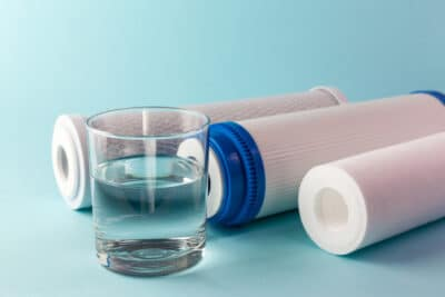 Three water filters next to a glass of water.