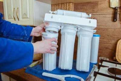 A person installing a water filter.