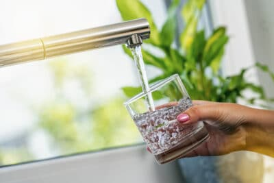 A sink filling a glass with water.