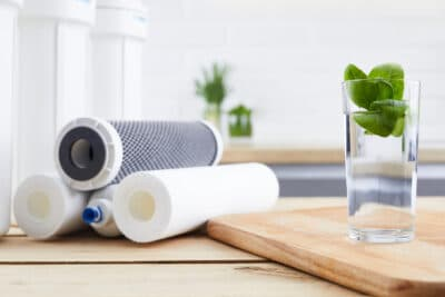 A glass of clean water with osmosis filter and cartridges in a kitchen interior.
