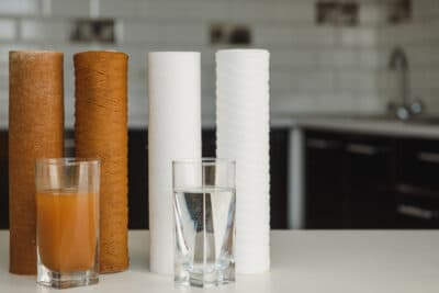 Used and new water filters behind glasses of dirty and clean water.