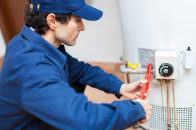 A plumber using a wrench on a water heater.