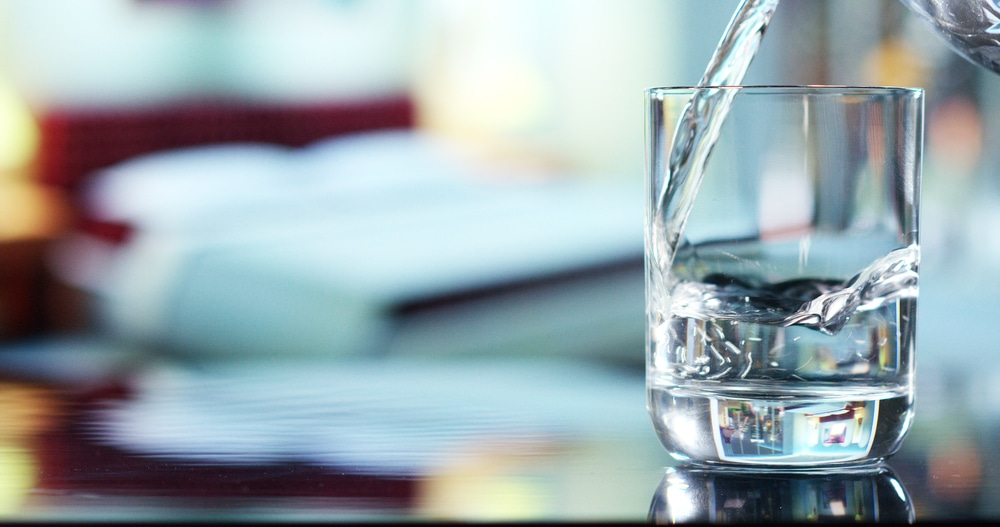 A glass of pure fresh water being poured into a glass.