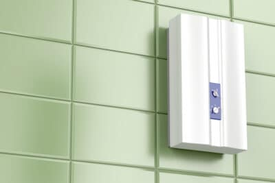 A tankless water heater attached to a bathroom wall.