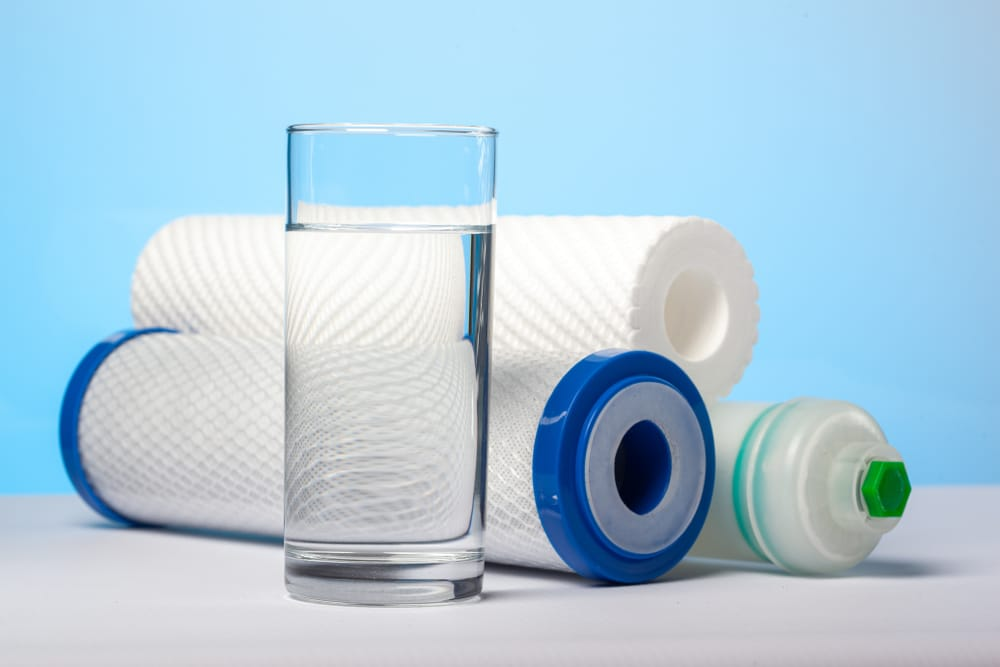 A glass of drink water and filter cartridges at bright blue background