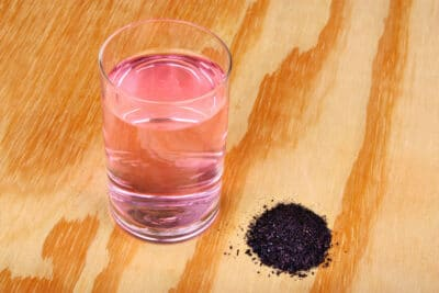 Pile of potassium permanganate crystals and glass a water on a wooden table