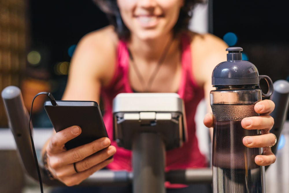 Healthy fit smiling woman training at home on exercise static bike during workout holding phone and bottle of water