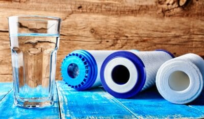 Carbon cartridges and a glass of water on a wooden background
