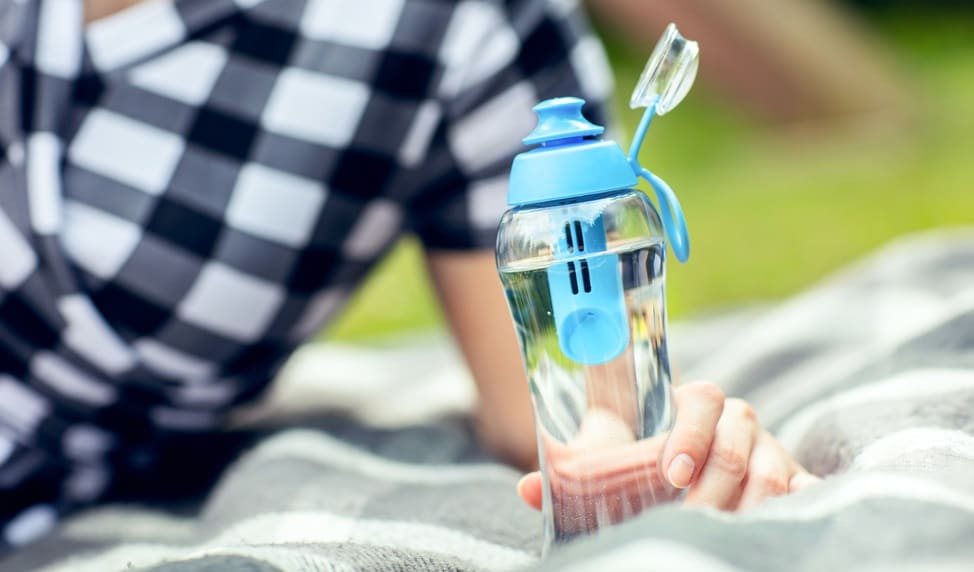 woman holds the bottle of filtered water outdoors
